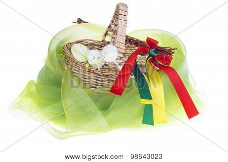 Close-up of isolated strawy basket on white background with Easter eggs