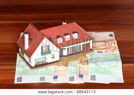 House And Money On Wooden Desk