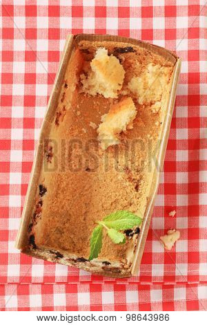 paper loaf pan with bits of  sponge cake