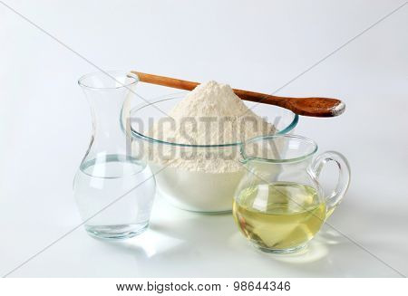 white wheat flour in a glass bowl with a wooden spoon, a carafe of cold water and a jug of sunflower oil