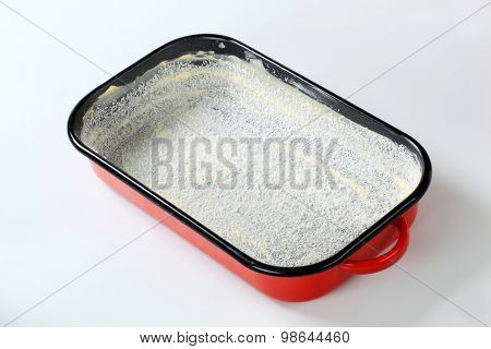 greased baking tin covered with desiccated coconut