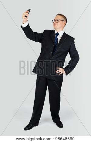 Portrait Of Young Handsome Business Man Taking A Selfie Photo With Smartphone Over The Gray Backgrou