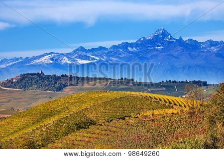 View on autumnal hills and vineyards with mountains on background in Piedmont, Northern Italy.