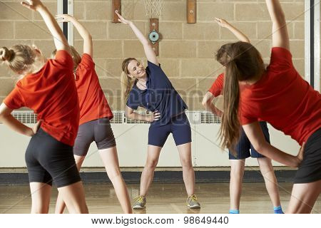 Teacher Taking Exercise Class In School Gym