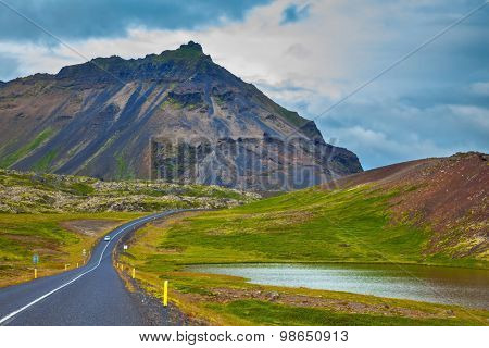 The road passes through the picturesque landscape in the mountains and lakes. Cloud Iceland in the summer