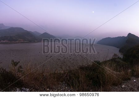 Autumn mist over Danube river at twilight with full moon over the river