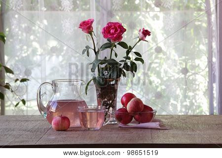 Compote From Apples In A Transparent Jug And A Bouquet Of Roses
