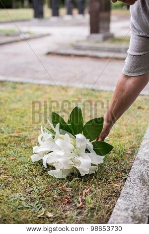 Woman Leaving Lilies On Grave
