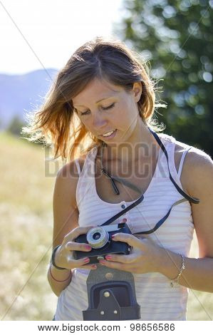 Beautiful Girl Portrait At The Field Holding A Retro Camera. Low Depth Of Field With Bokeh Backgroun