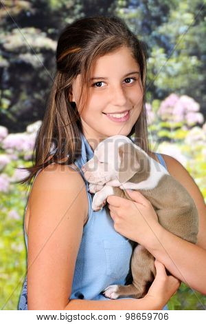 A beautiful young teen happily holding her baby pit bull.