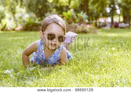 Cute Little Girl With Glasses Laying In The Grass On A Sunny Summer Day