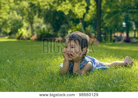 Cute Little Girl Laying In The Grass On A Sunny Summer Day