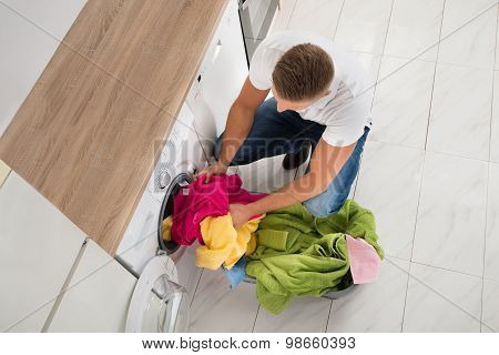 Man Putting Clothes In Washing Machine
