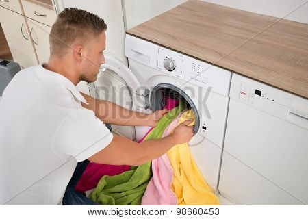 Man Loading Towels Into The Washing Machine
