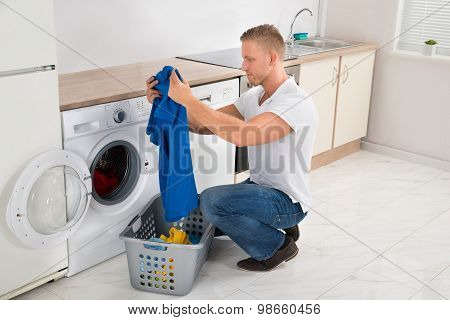 Man With T-shirt While Using Washing Machine