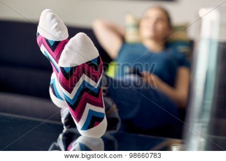 Woman With Feet On Table Watching Film Tv At Home