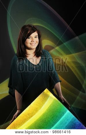 Portrait of a happy young teen leaning over a bright triangle and before swirls on black.