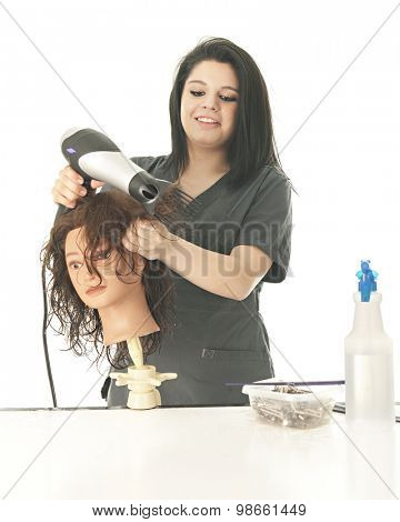 A pretty young cosmetology student laughing as she styles her practice mannequin's hair.  On a white background.