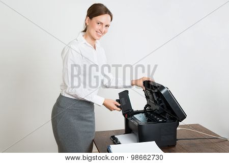 Businesswoman With Laser Cartridge And Printer At Desk