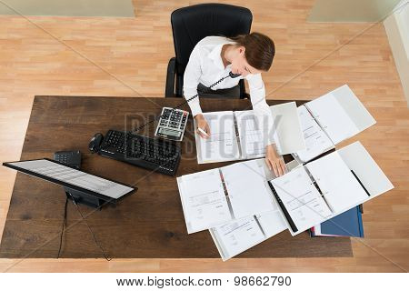 Businesswoman Attending Call While Calculating Finance