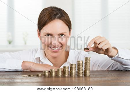 Businesswoman Placing Coin To Stack Of Coins