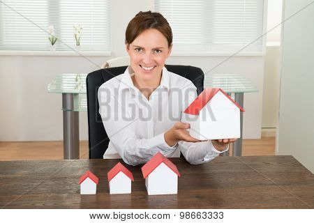 Businesswoman With House Models On Desk