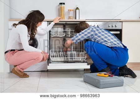Woman Looking At Repairman Repairing Dishwasher