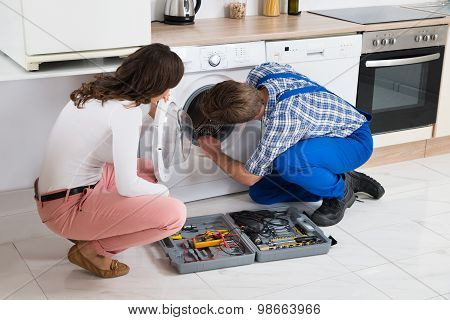 Repairman Repairing Washer In Front Of Woman