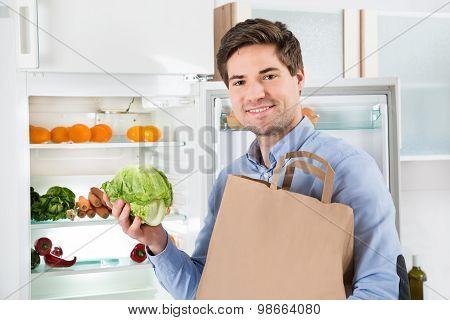 Man With Grocery Bag Standing Near The Open Fridge