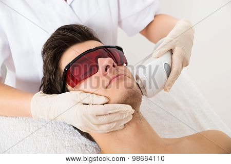 Beautician Giving Laser Epilation Treatment To Man Face