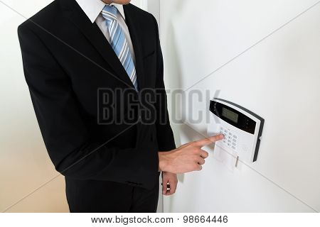 Businessman Setting Home Security Alarm System