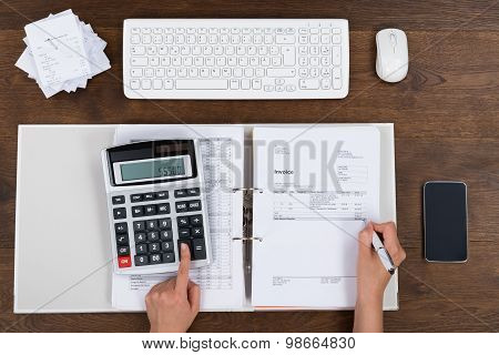 Person Calculating Invoice With Calculator