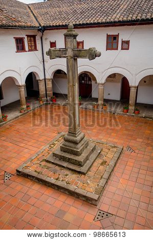 Large stone cross located inside courtyard of San Diego church, beautiful colonial white building st