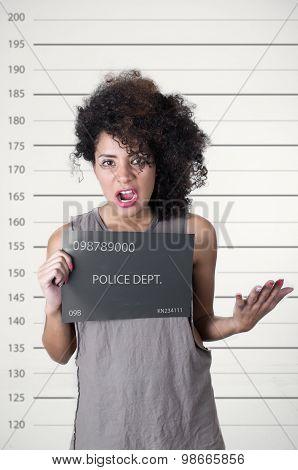 Hispanic brunette model afro like hair wearing grey sleeveless shirt holding up police department bo