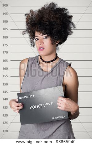 Hispanic brunette rebel model afro like hair wearing grey sleeveless shirt holding up police departm