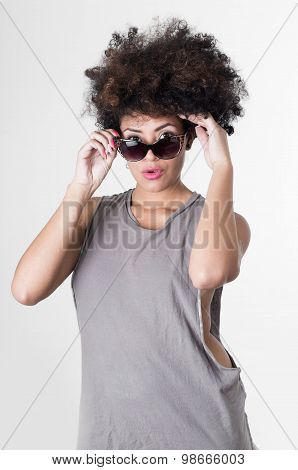 Hispanic brunette rebel model with afro like hair wearing grey sleeveless shirt putting on sunglasse