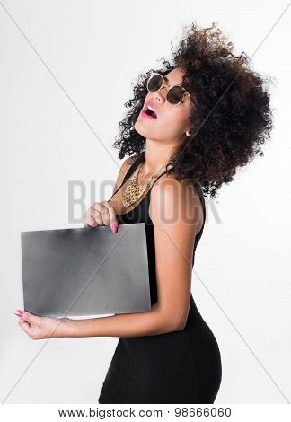Hispanic model wearing black sexy dress and sunglasses holding blank board looking upwards, shot fro