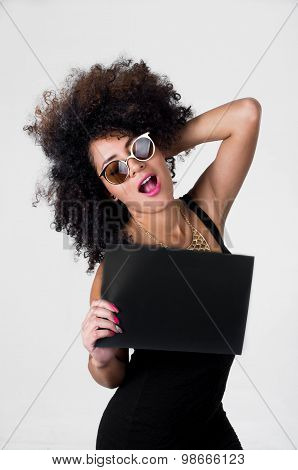 Hispanic model wearing black sexy dress and sunglasses holding blank board with right arm, left touc