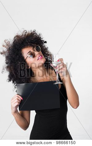 Hispanic model wearing black sexy dress and sunglasses holding blank board with right arm, glass of