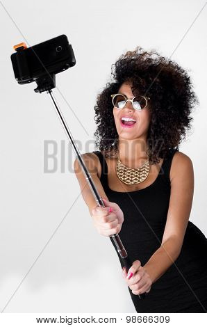 Hispanic model wearing sexy black dress, wild curly hair, golden necklace and sunglasses posing for