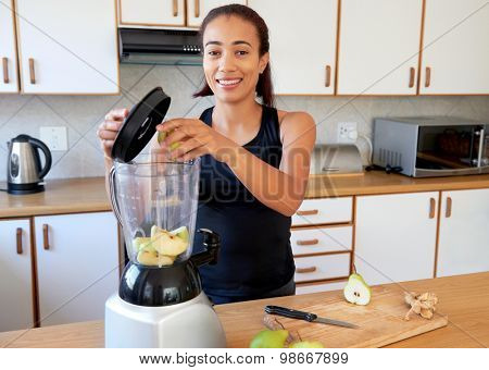 happy healthy female putting fruits into a blender preparing a smoothie