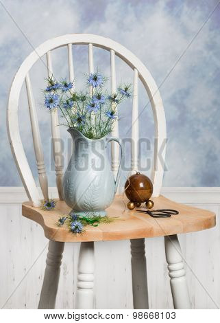 Still life with pretty cornflowers in antique jug sitting on chair
