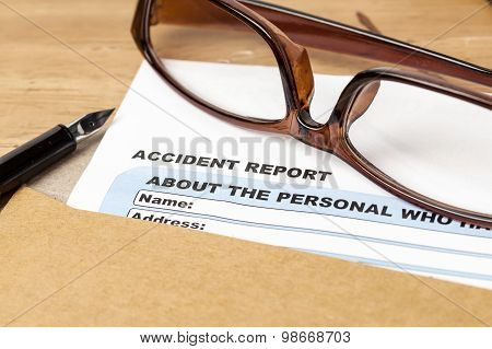 Accident Report Application Form And Pen On Brown Envelope And Eyeglass, Business Insurance And Risk