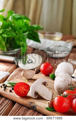 Food Ingredients For Pizza Or Pasta Dishes On A Wooden Table In The Rustic Kitchen