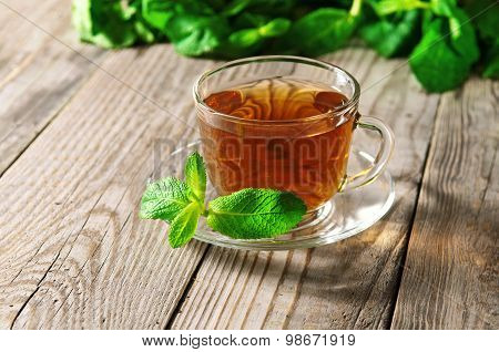 glass cup of tea with a mint leaf on a saucer on a wooden table closeup.