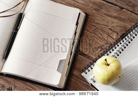 blank diary on wooden table with apple closeup.