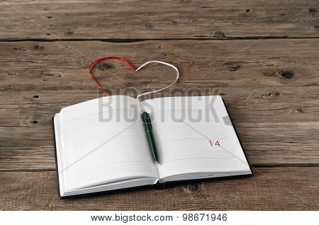 Open blank notebook on a wooden table. With ropes of notebook made heart