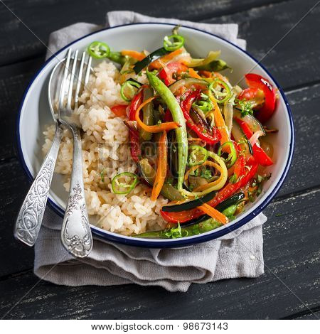 Rice With Vegetable Stir-fry On White Enamel Dish On Dark Wooden Background