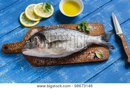 Fresh Dorado Fish And Lemon On A Blue Wooden Background