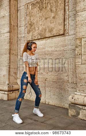 Girl Listening To Music On Headphones And Dancing In City.